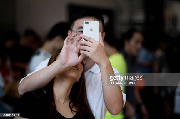 Chinese couple tests the new iPhone 7 during the opening sale launch at an Apple store in Shanghai on September 16 2016 With new iPhones hitting the...