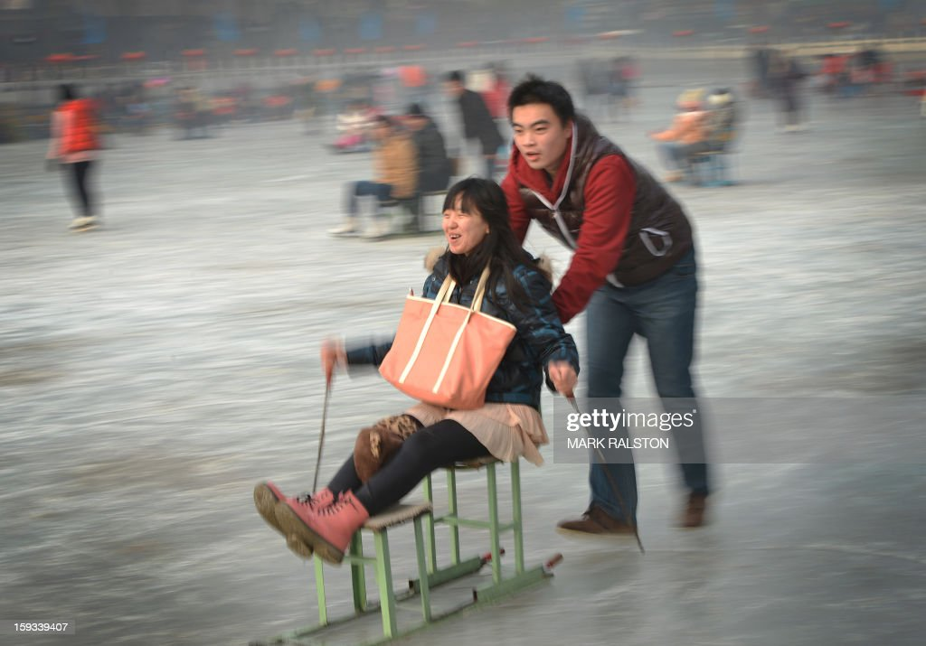 A Chinese couple use a sled on the frozen Houhai Lake in Beijing on January 12, 2013. The lake attracts scores of tourists and locals who use its frozen surface for skating, ice swimming and even exercising their dogs despite winter temperatures of up to minus 18 Celsius (0 F). AFP PHOTO/Mark RALSTON
