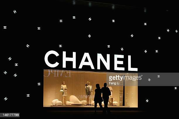 Chinese couple walk past the Chanel store on June 8 2012 in Beijing China According to the World Luxury Association 2011 annual official report China...