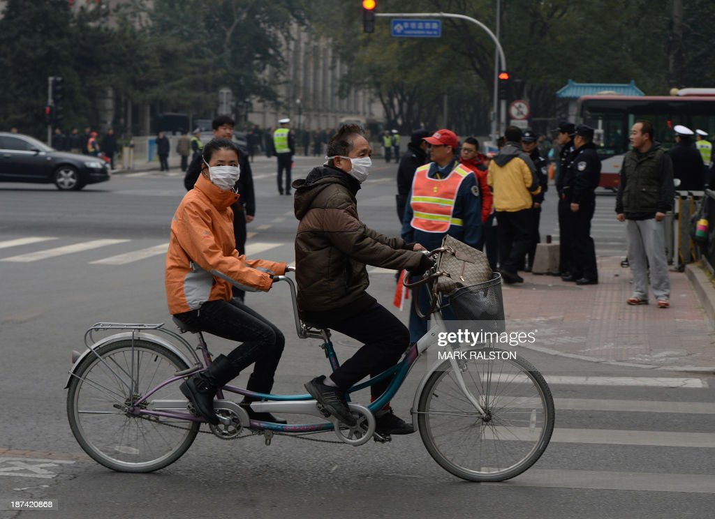 A Chinese couple wear face mask to protect against air pollution as they ride past the Jingxi Hotel which is the site of the Communist Party Central Committee's Third Plenum in Beijing on November 9, 2013. China's ruling Party started the key meeting which is expected to focus on economic reforms a year after a closely watched leadership transition. The four-day session of the full 376-member Communist Party Central Committee takes place at a closely guarded private hotel and traditionally sets the economic tone for a new government. AFP PHOTO/Mark RALSTON