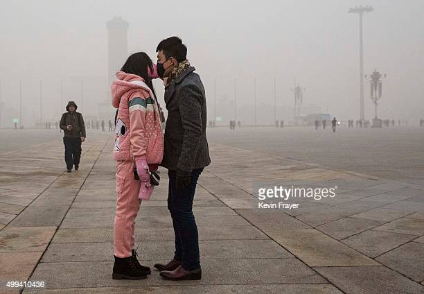 Chinese couple wear masks as they kiss during a day of high pollution in Tiananmen Square on December 1 2015 in Beijing China China's capital and...