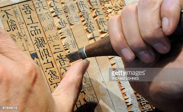 A Chinese craftsman carves characters onto a woodblock as he demonstrates traditional techniques of Chinese printing at the Chinese pavilion of the...
