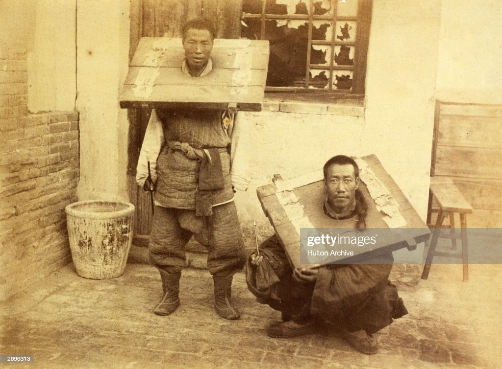 Chinese criminals are restrained in wooden stocks.