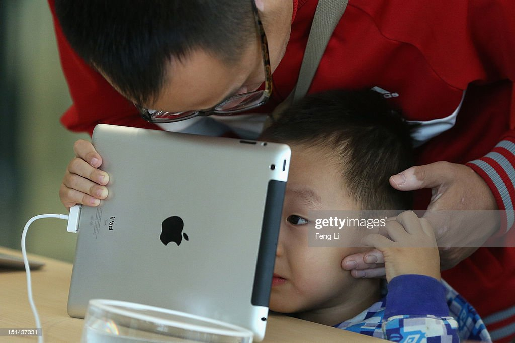 A Chinese customer and his son look at the iPad in the newly opened Apple Store in Wangfujing shopping district on October 20, 2012 in Beijing, China. Apple Inc. opened its sixth retail store on the Chinese mainland Saturday. The new Wangfujing store is Apple's largest retail store in Asia.