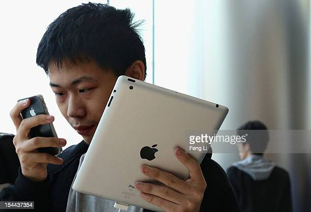 Chinese customer looks at his iPhone 4S with a iPad in other hand in the newly opened Apple Store in Wangfujing shopping district on October 20 2012...