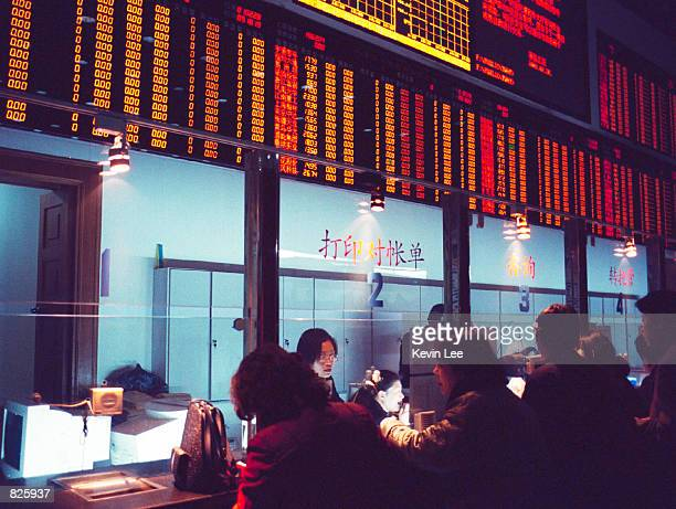 Chinese customers fill out paperwork early in the morning February 28 2001in a Beijing stock exchange Days after China announced the opening of its...