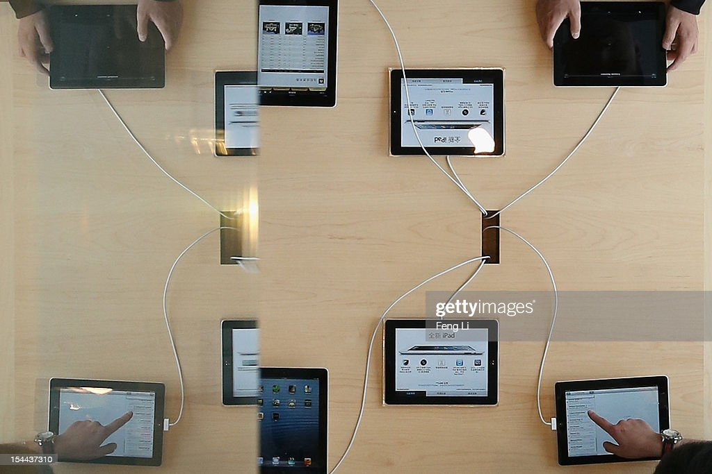 Chinese customers look at iPad HD in the newly opened Apple Store in Wangfujing shopping district on October 20, 2012 in Beijing, China. Apple Inc. opened its sixth retail store on the Chinese mainland Saturday. The new Wangfujing store is Apple's largest retail store in Asia.
