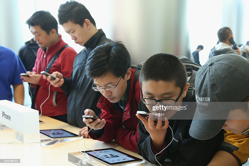 Chinese customers look at iPhone 4S in the newly opened Apple Store in Wangfujing shopping district on October 20, 2012 in Beijing, China. Apple Inc. opened its sixth retail store on the Chinese mainland Saturday. The new Wangfujing store is Apple's largest retail store in Asia.