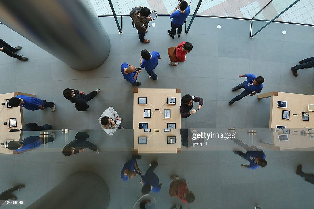 Chinese customers look at the iPad in the newly opened Apple Store in Wangfujing shopping district on October 20, 2012 in Beijing, China. Apple Inc. opened its sixth retail store on the Chinese mainland Saturday. The new Wangfujing store is Apple's largest retail store in Asia.