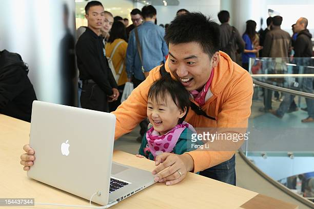 Chinese customers look at the MacBook Pro in the newly opened Apple Store in Wangfujing shopping district on October 20 2012 in Beijing China Apple...