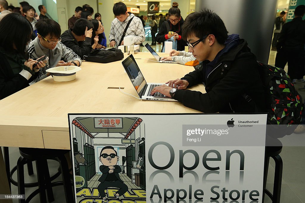 Chinese customers look at the MacBook Pro in the newly opened Apple Store in Wangfujing shopping district on October 20, 2012 in Beijing, China. Apple Inc. opened its sixth retail store on the Chinese mainland Saturday. The new Wangfujing store is Apple's largest retail store in Asia.