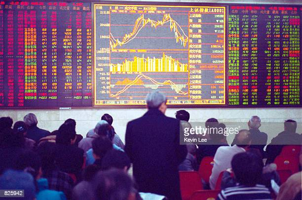 Chinese customers look at the stock index on the first day of B share trading February 28 2001 at the stock exchange in Beijing China Days after...