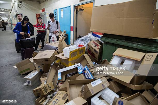 Chinese customers stand next to a pile of disposed packaging as they carry bags of purchased goods while waiting for a lift before leaving a...