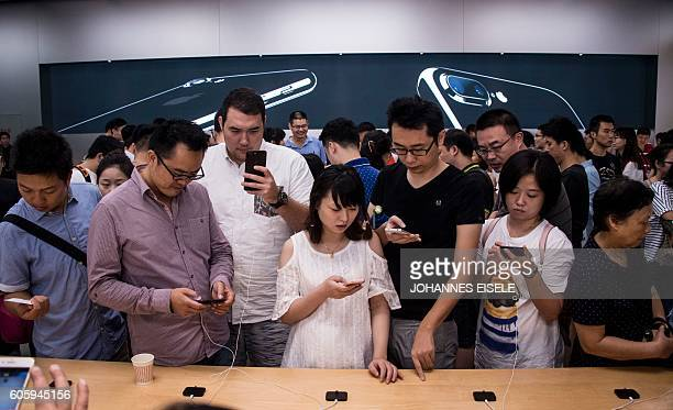 Chinese customers test the new iPhone 7 during the opening sale launch at an Apple store in Shanghai on September 16 2016 With new iPhones hitting...