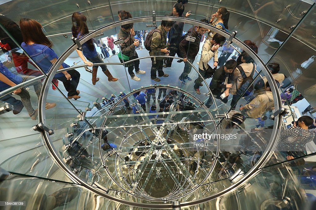 Chinese customers walk along the spiral steps of the newly opened Apple Store in Wangfujing shopping district on October 20, 2012 in Beijing, China. Apple Inc. opened its sixth retail store on the Chinese mainland Saturday. The new Wangfujing store is Apple's largest retail store in Asia.