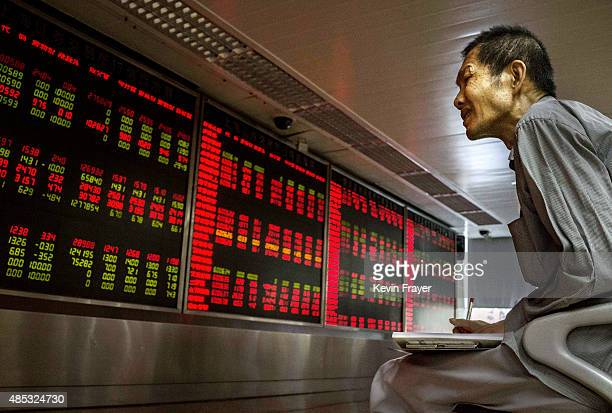 Chinese day trader takes notes on the activity of the market he watches a stock ticker at a local brokerage house on August 27 2015 in Beijing China...