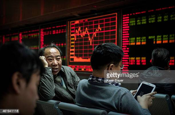 Chinese day traders chat as they sit in front of stock tickers on a board at a brokerage firm on January 22 2015 in Beijing China China's economic...