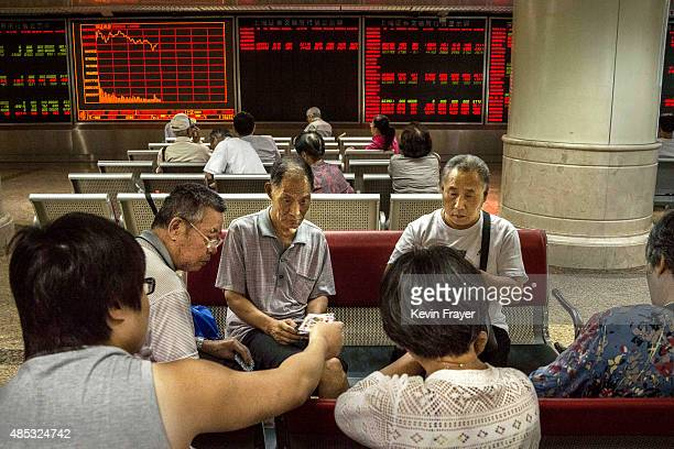 Chinese day traders play cards at a local brokerage house on August 27 2015 in Beijing China A dramatic selloff in Chinese stocks caused turmoil in...