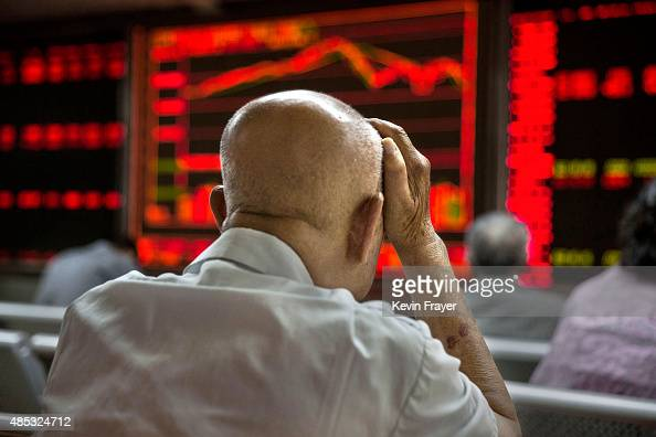 Chinese day traders watch stock tickers at a local brokerage house on August 27 2015 in Beijing China A dramatic selloff in Chinese stocks caused...