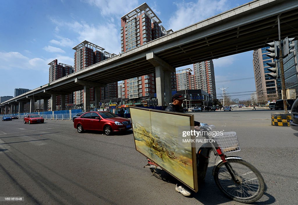 A Chinese deliveryman rides past a new property development in Beijing on April 1, 2013. Chinese home prices picked up in March as buyers rushed to beat new government policies aimed at cracking down on speculation. China issued new rules in March to rein in prices, including a nationwide capital gains tax of 20 percent on profits owners make from selling residential property. AFP PHOTO/Mark RALSTON
