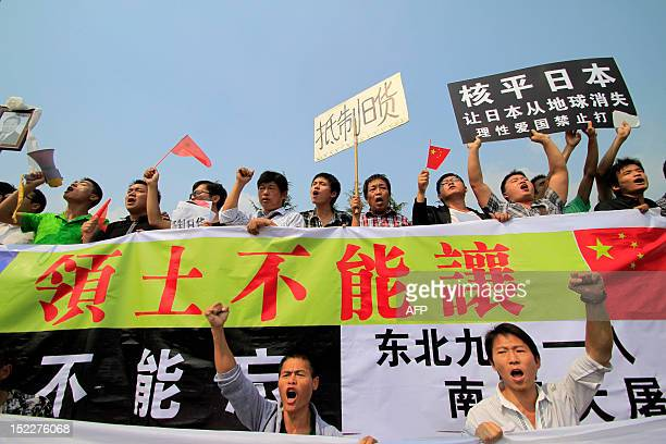 Chinese demonstrators carry Chinese national flags and shout slogans during a protest against Japan's 'nationalizing' of the Diaoyu Islands also...