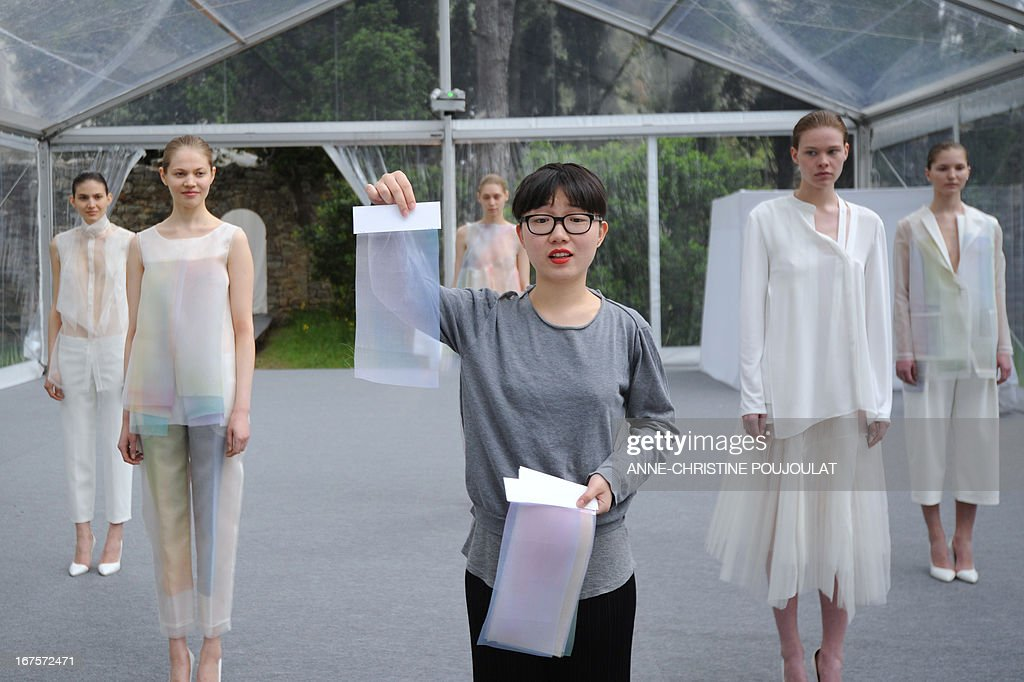 Chinese designer Shanshan Ruan (C) presents to the jury her creations worn by models on April 26, 2013, during the 28th edition of the International Festival of Fashion and Photography in the French southern city of Hyeres. This year's President of the Jury is Portuguese fashion designer Felipe Oliveira Baptista. AFP PHOTO /ANNE-CHRISTINE POUJOULAT