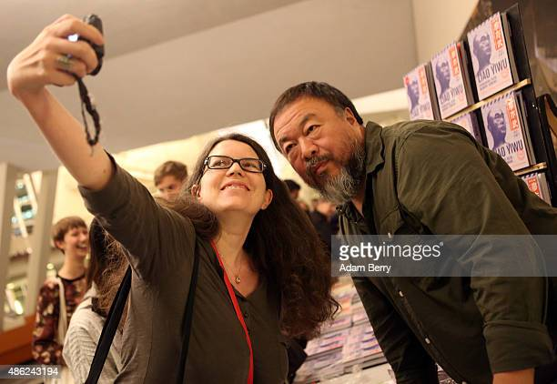 Chinese dissident artist Ai Weiwei poses for a selfie with fan Isabelle Spicer as he gives autographs after a panel discussion at the Berlin...