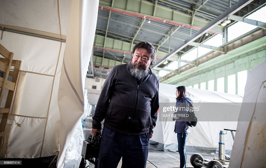 Chinese dissident artist Ai Weiwei talks with members of his camera team as he visits a refugee shelter at Berlin's former Tempelhof airport on February 10, 2016. Ai Weiwei plans to make a film on the worldwide refugee crisis. / AFP / dpa / Kay Nietfeld / Germany OUT
