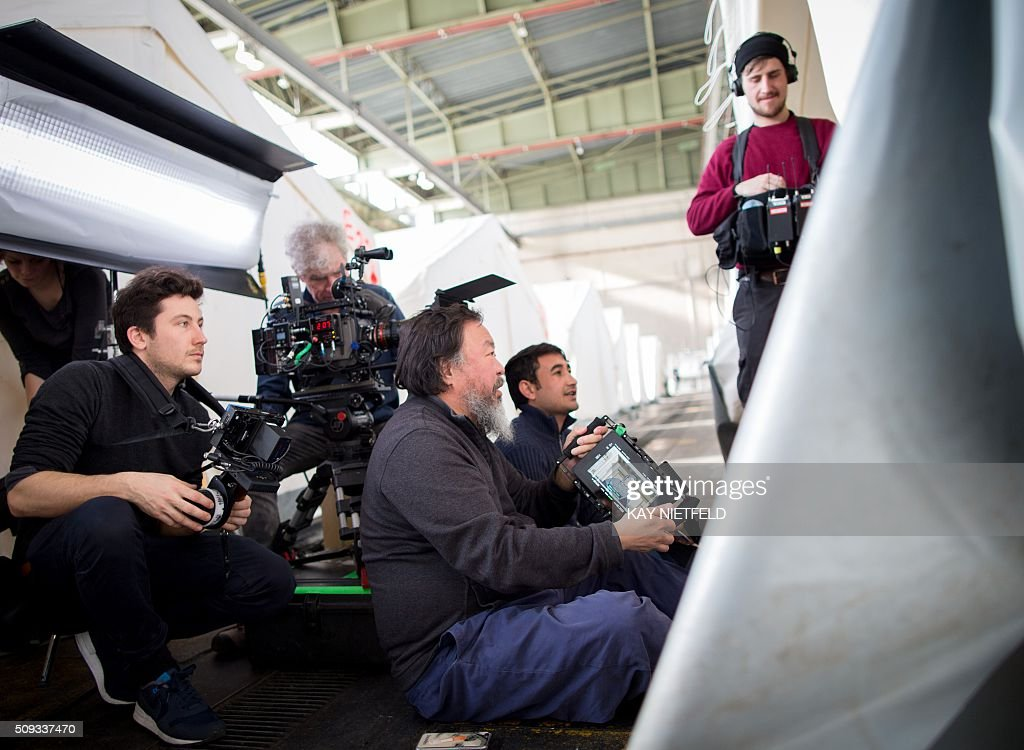 Chinese dissident artist Ai Weiwei (C) talks with members of his camera team as he visits a refugee shelter at Berlin's former Tempelhof airport on February 10, 2016. Ai Weiwei plans to make a film on the worldwide refugee crisis. / AFP / dpa / Kay Nietfeld / Germany OUT