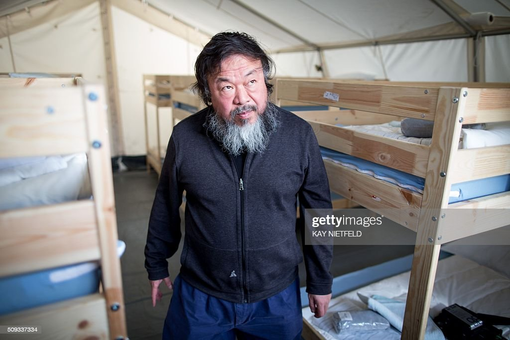 Chinese dissident artist Ai Weiwei visits a refugee shelter at Berlin's former Tempelhof airport on February 10, 2016. Ai Weiwei plans to make a film on the worldwide refugee crisis. / AFP / dpa / Kay Nietfeld / Germany OUT