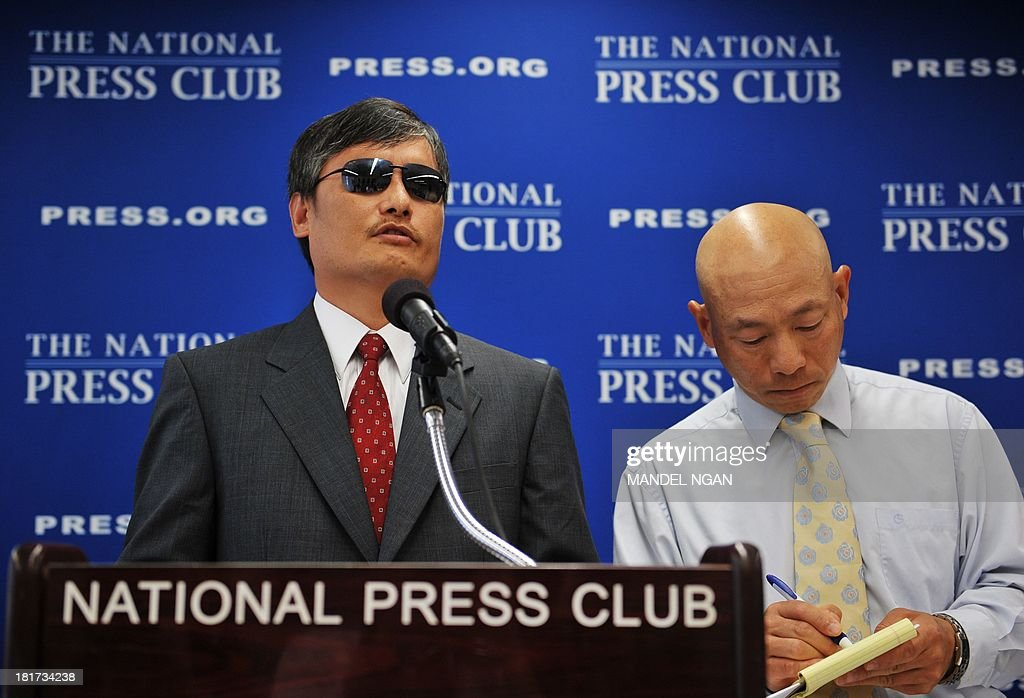 Chinese dissident Chen Guangcheng speaks on China's treatment of dissidents and their families while his translator takes notes during a press conference at the National Press Club on September 24, 2013 in Washington, DC. AFP PHOTO/Mandel NGAN