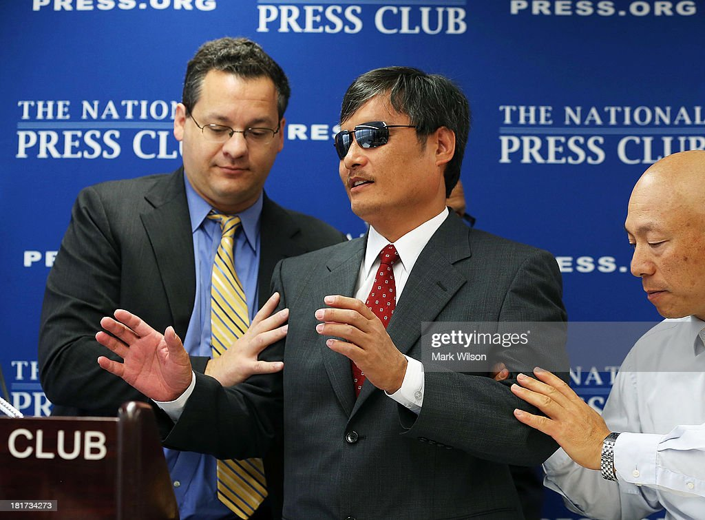 Chinese dissident Chen Guangcheng who is blind is guided to the podium by Jared Genser of Freedom Now before speaking at the National Press Club...