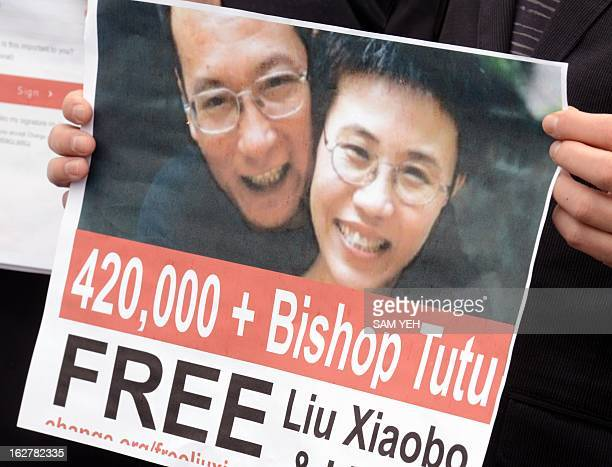 Chinese dissident Wang Dan displays a poster of Liu Xiaobo in front of Taiwan 's presidential office calling Taiwan's President Ma Yingjeou to help...