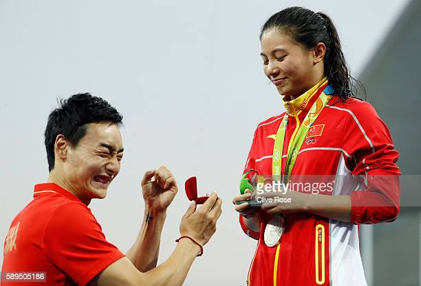 Chinese diver Qin Kai proposes to silver medalist He Zi of China on the podium during the medal ceremony for the Women's Diving 3m Springboard Final...