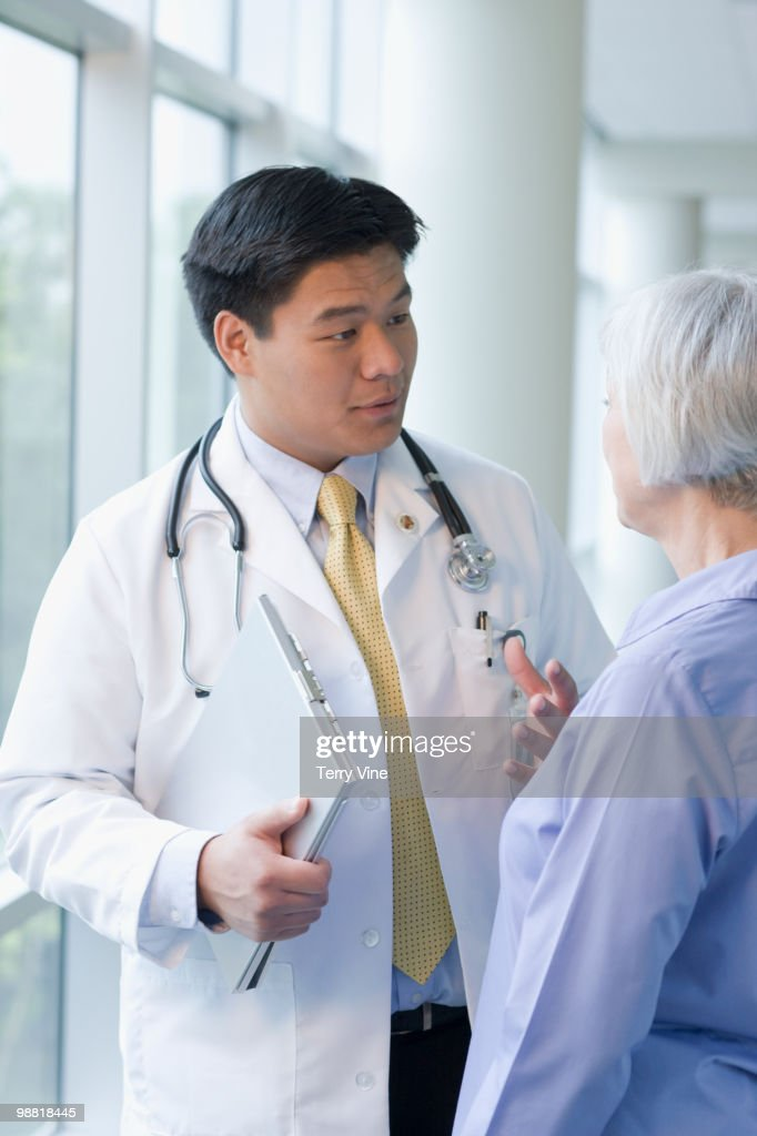 Chinese doctor talking to woman : Stock Photo