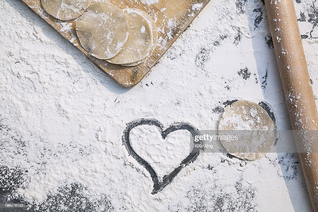 Chinese dumpling making, heart in the flour : Stock Photo