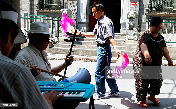 Chinese elderly people enjoy entertainment on a sidewalk on June 14 2005 in Beijing China China will have about 400 million elderly people by the...