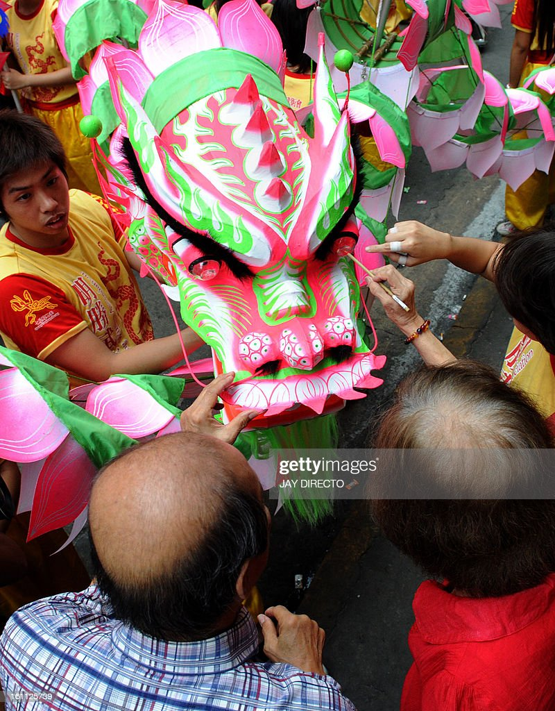 Chinese elders apply eyelids to a newly made lotus dragon during a blessing on the eve of the Chinese Lunar New Year of the Snake in the streets of China town in Manila on February 9, 2013. T he Dragon Dance is usually performed during the Chinese New Year to bring in good luck and prosperity as billions of Chinese world wide celebrate Lunar New Year of the Snake. AFP PHOTO / Jay DIRECTO