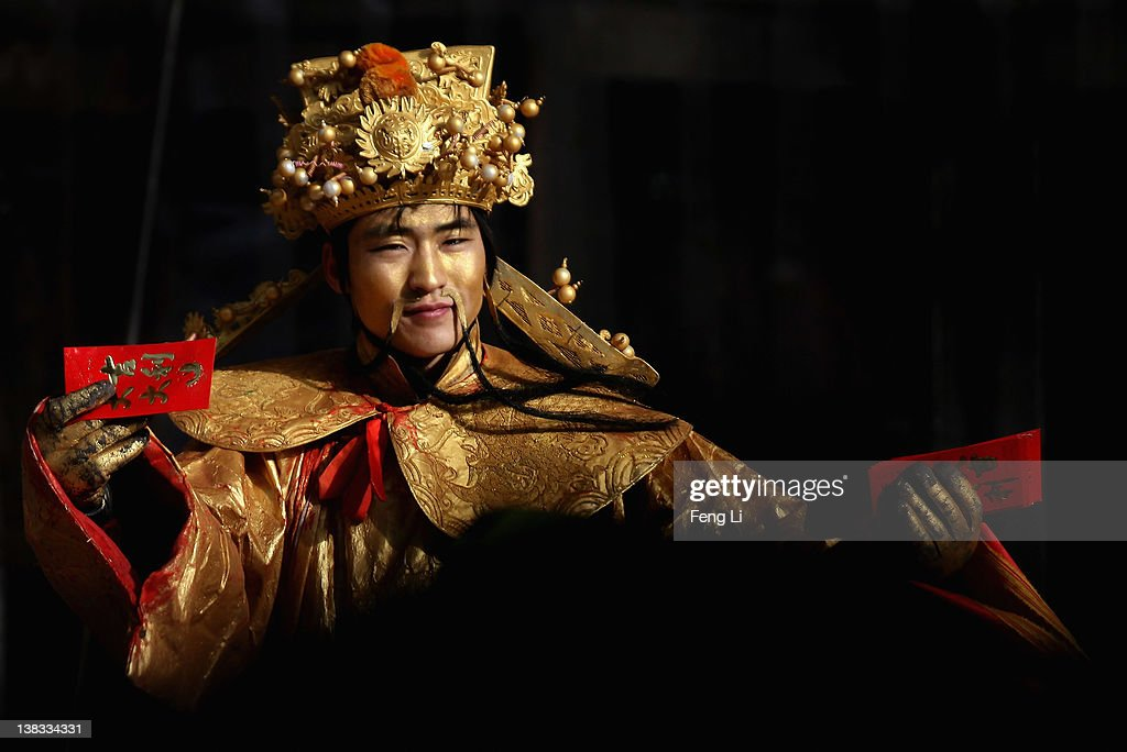 A Chinese employee dresses as gods of fortune to attract customers while distributing discount vouchers at the entrance of a shopping mall during the Chinese Lantern Festival on February 6, 2012 in Beijing, China. The Chinese Lantern Festival, also known as Yuanxiao Festival, falls on February 6 this year in China.