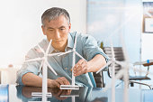 Chinese engineer examining model wind turbines in office