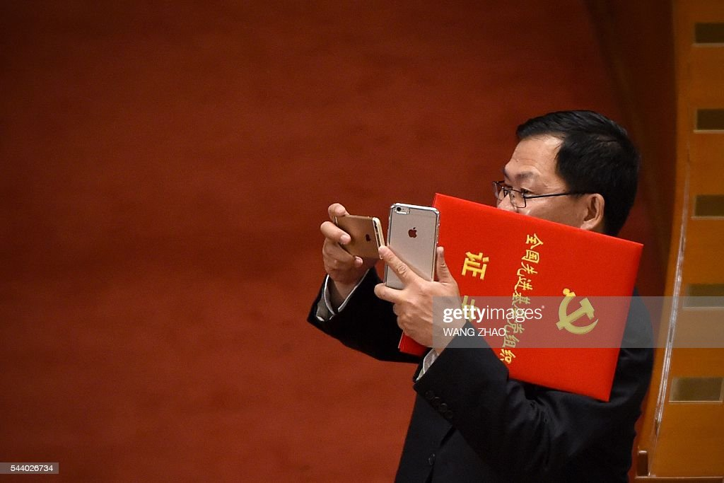 A Chinese ethnic minority communist party member uses a mobile phone to take a photo during the Celebration Ceremony of the 95th Anniversary of the Founding of the Communist Party of China at the Great Hall of the People in Beijing on July 1, 2016. China's Communist Party take the ruling organisation's membership to almost 88 million and the anniversary of the Party's founding falls on July 1. / AFP / WANG