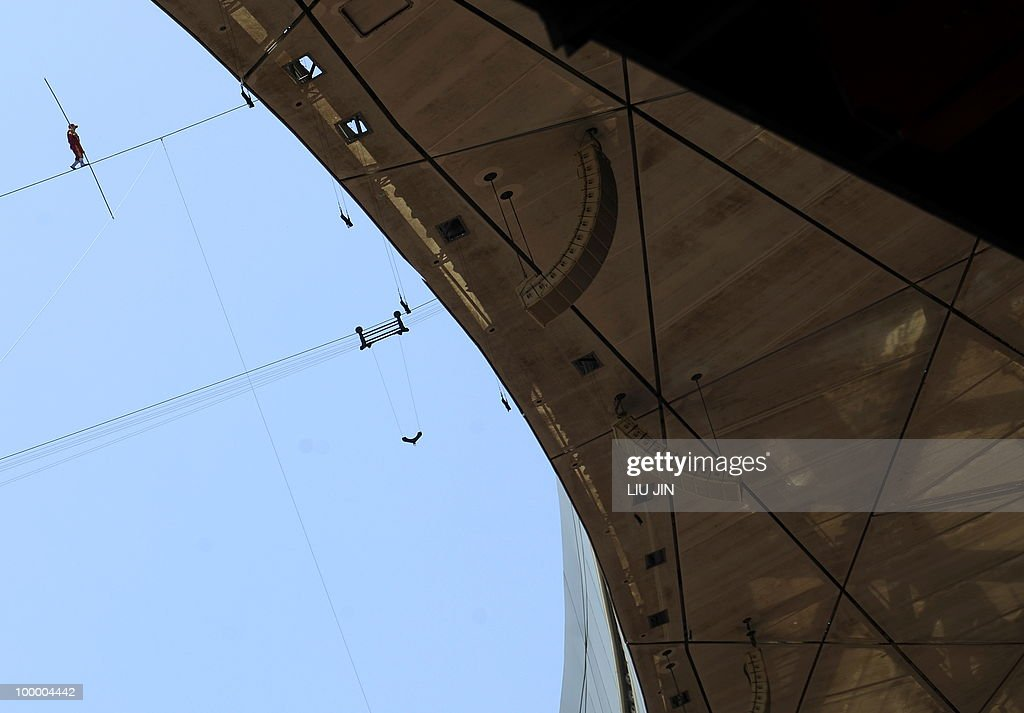 Chinese ethnic Uighur acrobat Adili Wuxor performs on a tightrope which is 60-meters high and 3.3 centimeters in diameter, above the National Stadium, known as the 'Bird's Nest' in Beijing on May 20, 2010. Adili will live in a small cabin and perform for five hours on the wire each day in the coming two months, to attempt to break the Guinness World Record for steel wire walking. AFP PHOTO/LIU Jin