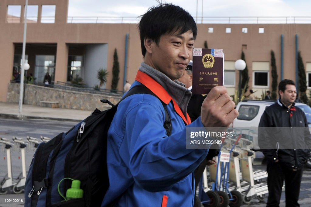 A Chinese evacuee from Libya shows his passport after he arrived at the port of Herakleion, on the Greek island of Crete on February 24, 2011. Thousands of Chinese and scores of Europeans began landing Thursday at the port of Heraklion on the Greek island of Crete after their evacuation from unrest-hit Libya aboard chartered Greek ferries. The first boat from the Libyan port of Benghazi, the ferry Hellenic Spirit, reached Heraklion after 1200 GMT and was followed by the ferry Olympic champion, an AFP photographer reported. AFP PHOTO / Aris Messinis