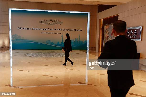 Chinese event staff walk past a sign ahead of the G20 Finance Ministers and Central Bank Governors Meeting at the Pudong Shangrila Hotel on February...