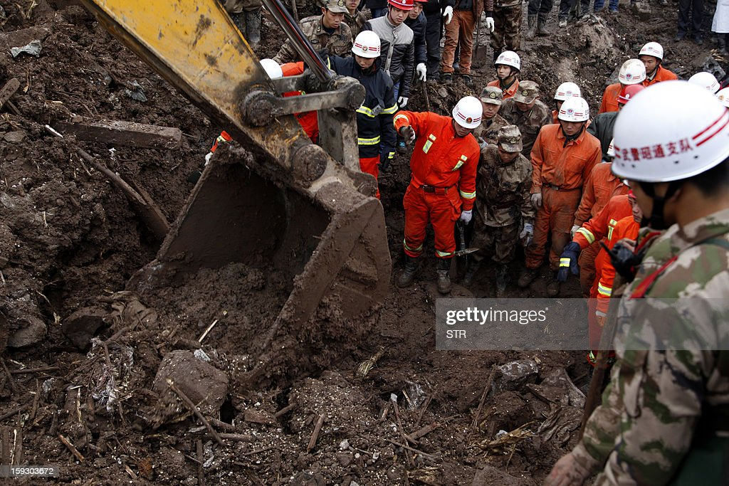 A Chinese excavator and rescue workers search for buried residents in a disaster-hit area in Gaopo village, southwest China's Yunnan province on January 11, 2013. A landslide killed at least 36 people including seven from a single family when it smashed into the village on January 11, state-run media said. CHINA OUT AFP PHOTO