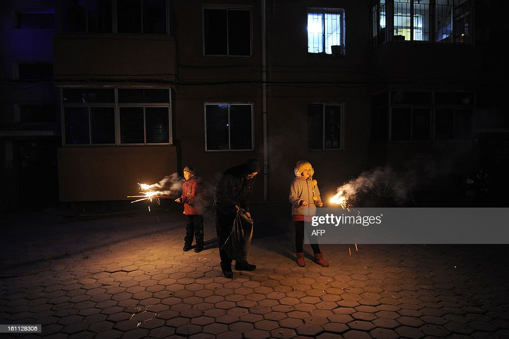 A Chinese family lights fireworks at a community centre in Fuxin, in the northeast Liaoning province on February 9, 2013, a day before the Lunar New Year. China is preparing to welcome the Lunar New Year of the Snake which falls on Febraury 10.