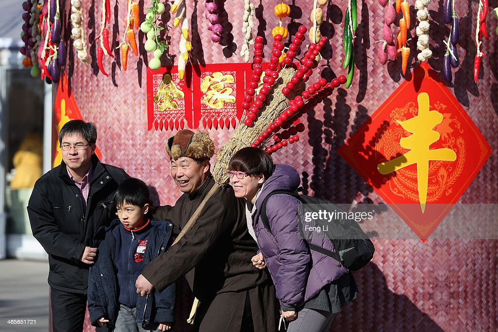 A Chinese family pose for photos with a folk artist at the Spring Festival Temple Fair for celebrating Chinese Lunar New Year of Horse at the Temple of Earth park on January 30, 2014 in Beijing, China. The Chinese Lunar New Year of Horse also known as the Spring Festival, which is based on the Lunisolar Chinese calendar, is celebrated from the first day of the first month of the lunar year and ends with Lantern Festival on the Fifteenth day.