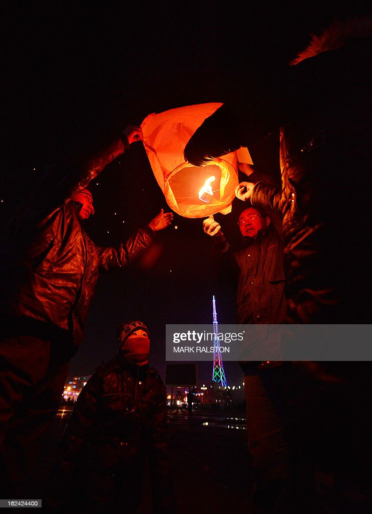A Chinese family release a paper lantern into the sky on the eve of the traditional Lantern Festival which falls on the 15th day of the Lunar New Year and officially ends the celebrations, in Yuxian on February 23, 2013. The festival which dates back more than 2000 years to the Han Dynasty sees China's cities become a sea of lanterns and fireworks. AFP PHOTO/Mark RALSTON