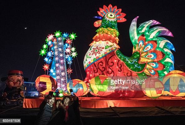 Chinese family take their picture in front of a large 'Fire Rooster' at a fair at a local park on the fifth day of the Chinese Lunar New Year on...
