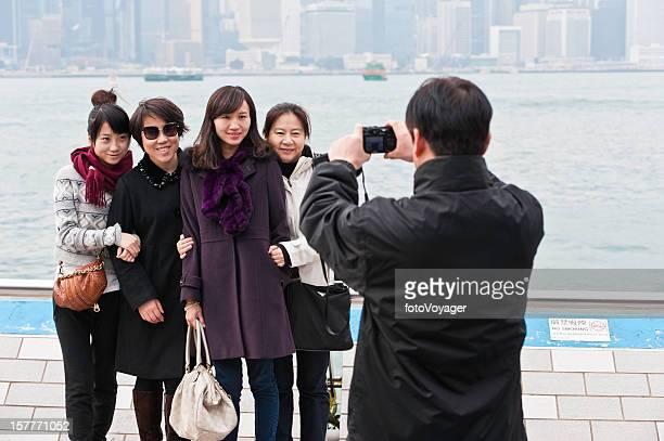 Chinese family tourists taking photo Hong Kong Harbor